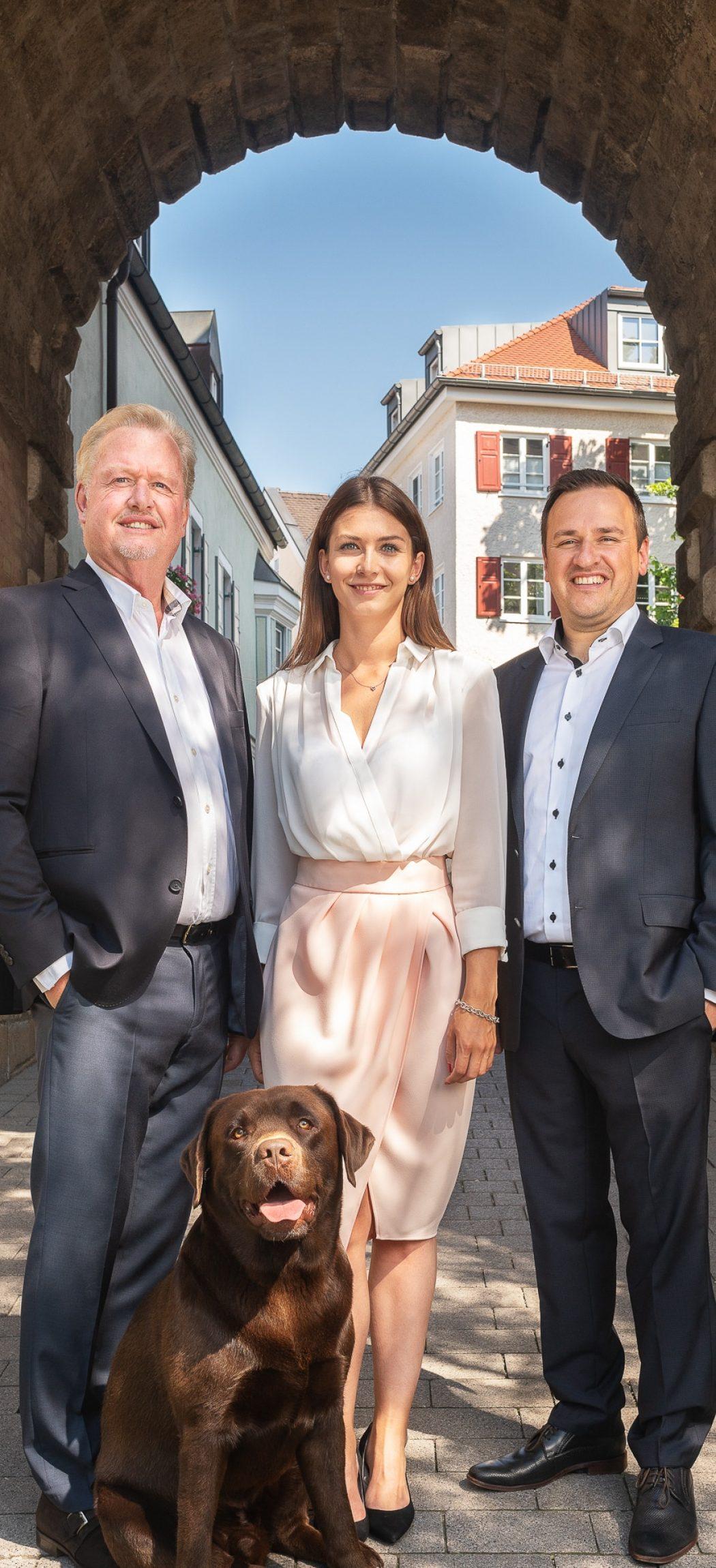 Zeigt die 3 Immobilienmakler von IFK Immobilien mit Hund
